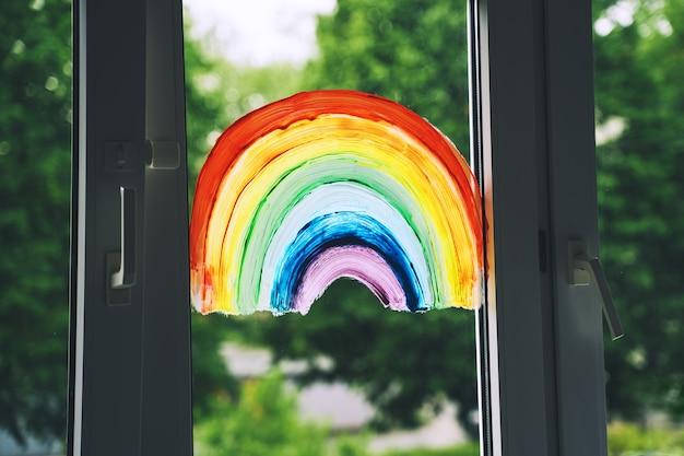 Крупным планом фото картины радуги на окне. нарисованная красками по стеклу радуга - это многозначный символ.