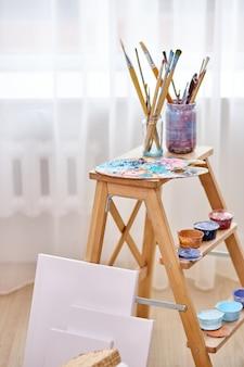 라이트 아트 스튜디오 룸에서 페인트, 붓, 이젤 및 캔버스의 근접 사진