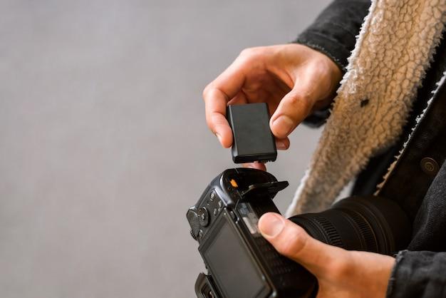 撮影前にカメラにバッテリーを挿入している写真家のクローズアップ写真。最新のカメラのバッテリー交換