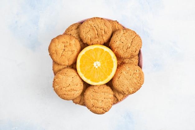 절반 잘라 오렌지와 쿠키 더미의 사진을 닫습니다.