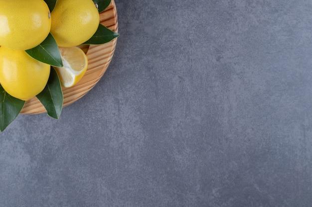 나무 접시에 레몬 더미의 사진을 닫습니다.