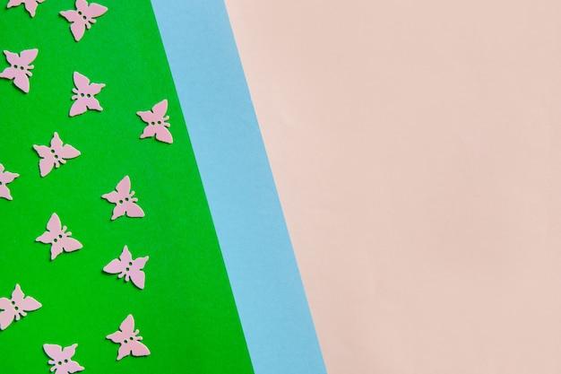 ピンクの蝶のクローズアップ写真は、カラフルなピンク、青、緑の背景に告白をキラキラと輝かせます。上面図、春、イースター、さまざまな休日やイベントのコンセプト