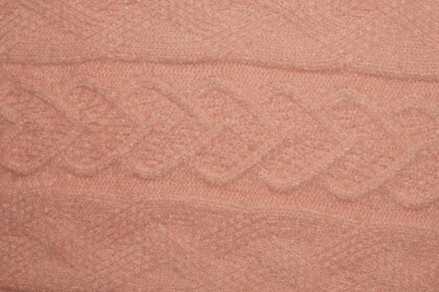 Крупным планом фото текстуры розовый вязаный свитер как абстрактный фон.