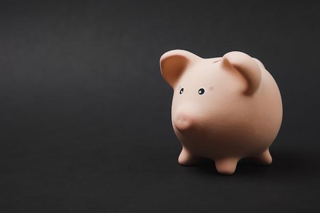 검은 벽 배경에 격리된 분홍색 돼지 저금통의 사진을 닫습니다. 돈 축적, 투자, 은행 또는 비즈니스 서비스, 부의 개념. 공간 광고를 조롱하십시오.