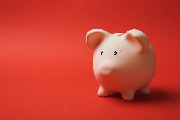 밝은 빨간색 벽 배경에 격리된 분홍색 돼지 저금통의 사진을 닫습니다. 돈 축적, 투자, 은행 또는 비즈니스 서비스, 부의 개념. 공간 광고를 조롱하십시오.