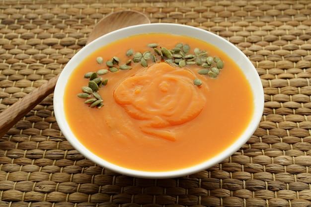 テーブルの上のカボチャの種とピューレカボチャスープの写真を閉じる