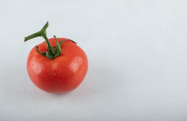 Крупным планом фото красных спелых помидоров на белом фоне.