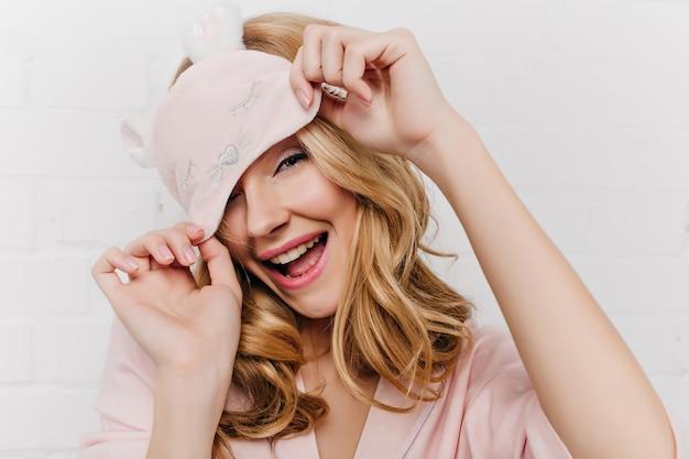 귀여운 수면 마스크와 함께 포즈를 취하는 우아한 매니큐어와 세련된 금발 소녀의 근접 사진. 아침에 장난하는 분홍색 옷에 꽤 백인 곱슬 여자.