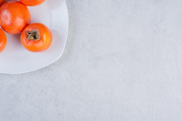 熟したオレンジ柿の果実のクローズアップ写真。白いお皿に。