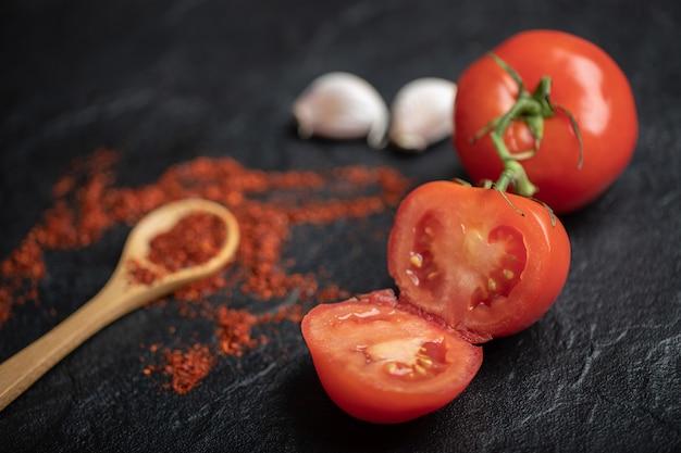 Крупным планом фото спелых помидоров целиком или наполовину с чесноком и красным острым перцем на черном фоне.
