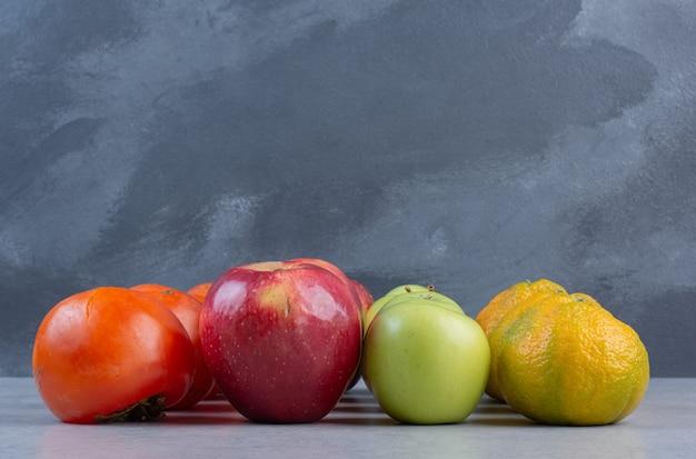 Крупным планом фото сезонных фруктов. яблоко хурмы и мандарины.