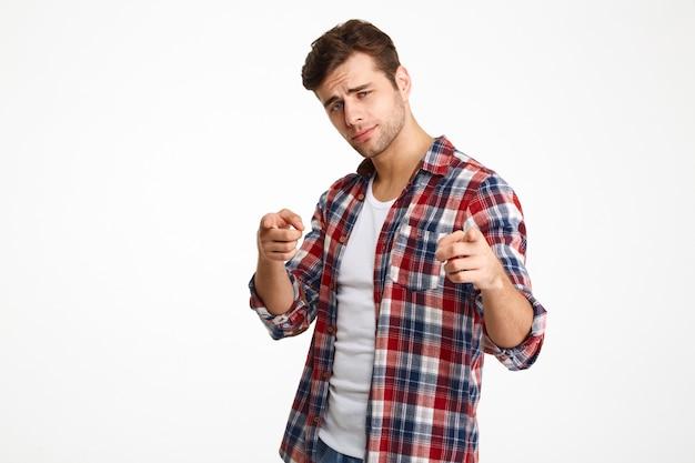 2本の指で指している市松模様のシャツで深刻な若い男のクローズアップ写真