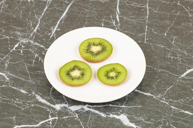 Крупным планом фото нарезанных киви на белой керамической тарелке