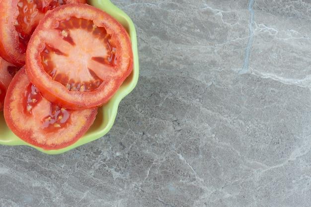 Крупным планом фото нарезанных красных помидоров в зеленой миске.