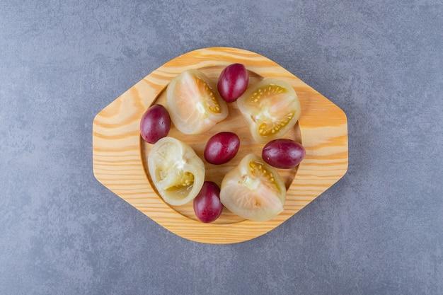 Закройте вверх по фото нарезанного томатного огурца на деревянной тарелке.
