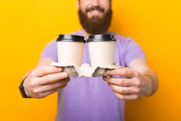 두 개의 종이 커피 컵을 들고 웃고 있는 수염난 힙스터 남자의 클로즈업 사진