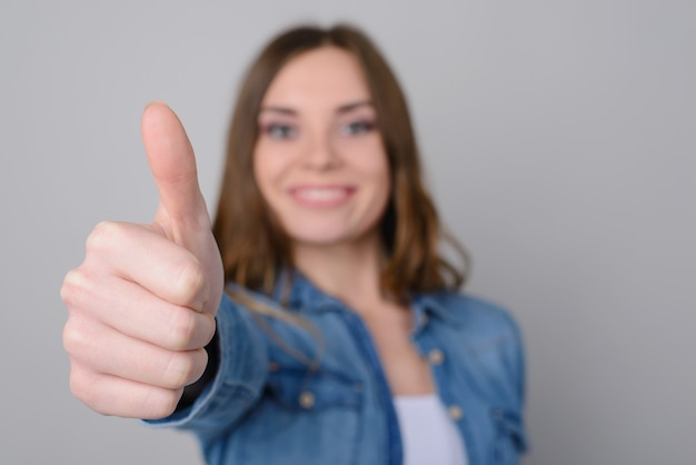 Закройте вверх по фото усмехаясь счастливой милой женщины в повседневной одежде показывая большой палец руки вверх. она изолирована на сером фоне
