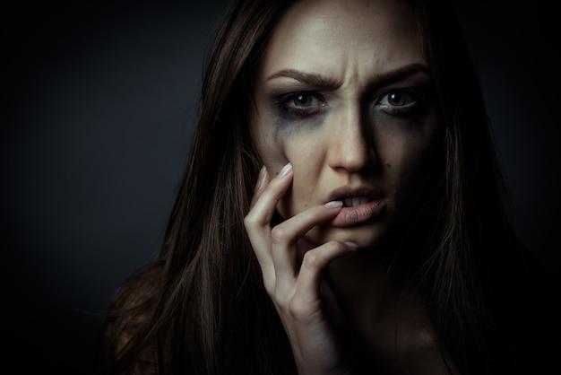 Крупным планом фото грустной грустной девушки, касающейся ее лица