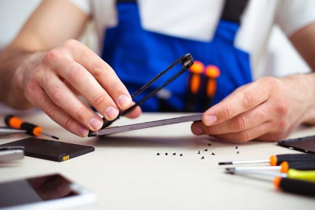 Крупным планом фото специалиста, ремонтирующего сломанный смартфон на своем рабочем месте с помощью профессиональных инструментов