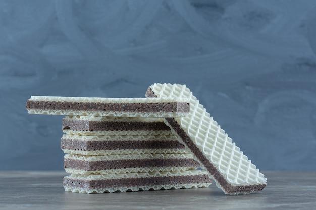 Крупным планом фото стога вафель на сером столе.