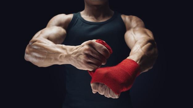 검은 배경에 손을 감싸는 강한 남자의 클로즈업 사진 남자는 검은 배경에 격리된 빨간색 권투 랩으로 손을 감싸고 있습니다. 강한 손과 주먹, 훈련 및 활동적인 운동 준비