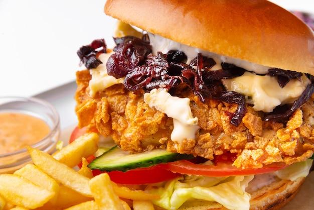 Крупным планом фото вкусного горячего бургера с хрустящей курицей и овощами на белой поверхности