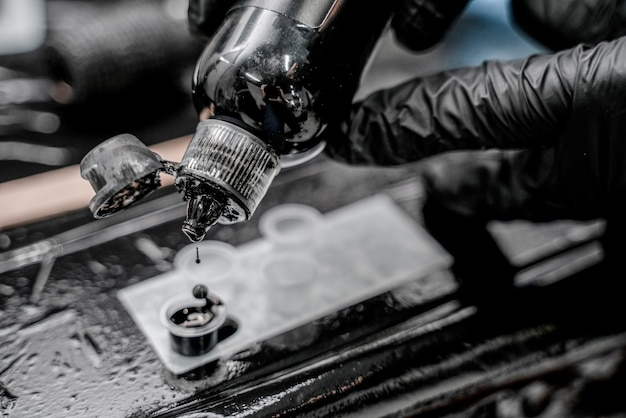 플라스틱 컵에 잉크를 붓는 검은 장갑을 낀 문신 마스터의 클로즈업 사진.