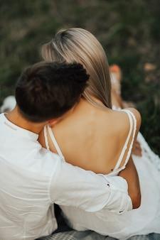 自然の中で一緒に優しい幸せなロマンチックなカップルの写真を閉じます。柔らかい首の後ろで女性に繊細にキスする男性。