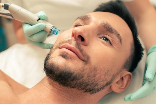 Крупным планом фото устройства для дермабразии возле лица мужчины во время процедуры увлажнения