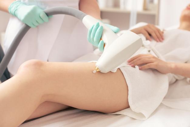 다리의 혈관망을 제거하는 동안 현대적인 도구를 사용하여 의료용 소파에 있는 여성의 다리 사진과 전문 전문가