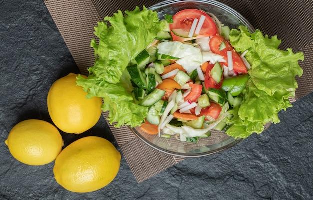野菜サラダと3つの新鮮なレモンの写真をクローズアップ。高品質の写真