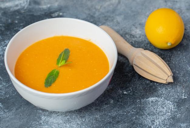레몬 압착기로 토마토 수프와 신선한 레몬의 사진을 닫습니다.