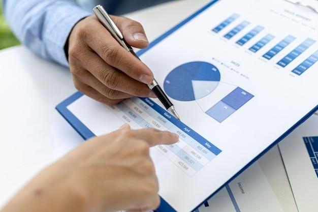 그래프 형식의 판매 데이터 시트를 가리키는 두 사업가의 클로즈업 사진, 그들은 판매 성장 관리라는 주제에 대해 함께 만나고 있습니다. 비즈니스 협력 및 판매 관리의 개념입니다.