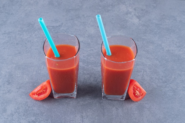 Закройте вверх по фото двух стаканов томатного сока и ломтиков томата.