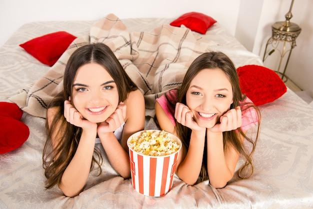 Крупным планом фото двух сестер, лежащих в постели с попкорном и улыбающихся