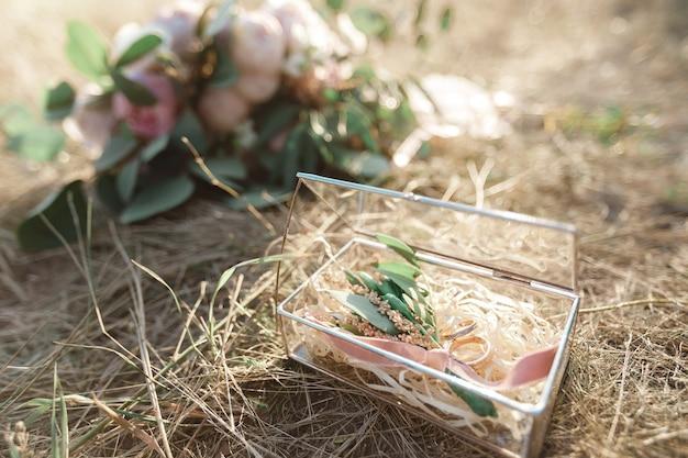 わらの背景に2つの結婚式の金の指輪の写真を閉じる