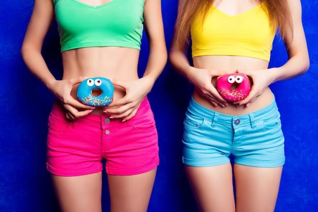 スリムな腹の近くでドーナツを保持している2人の女性のクローズアップ写真