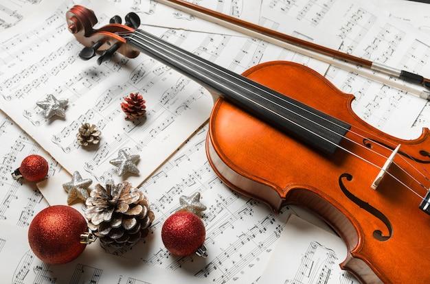 Крупным планом фото скрипки, музыкальных нот и рождественских украшений