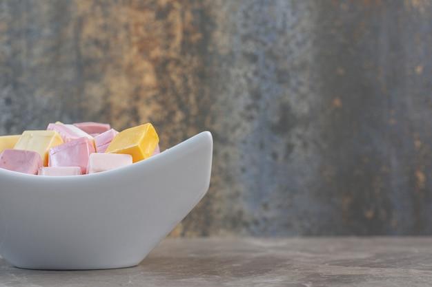 Закройте вверх по фото белой керамической миски, полной красочных кубических конфет. розовые, белые и желтые конфеты.