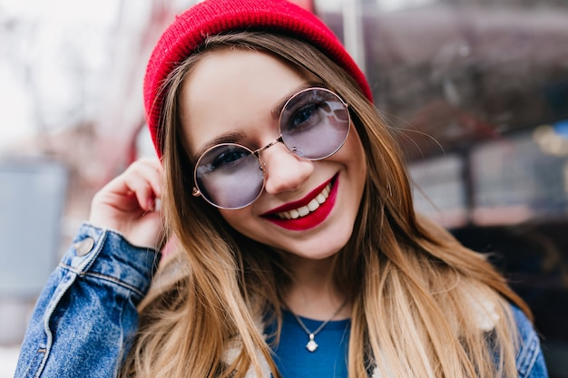 春の週末に街でリラックスしている白人の女の子のクローズアップ写真。デニムジャケットと青いメガネの素晴らしいヨーロッパの女性の屋外ショット。