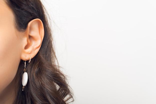 白い背景の上の女性の耳の写真を閉じる