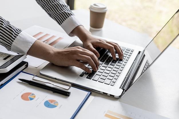 ラップトップのキーボードでタイピングするスーツを着た女性のクローズアップ写真、オンラインメッセンジャーを介してビジネスパートナーとチャットをタイプするビジネスウーマン。コミュニケーションにおけるテクノロジーの使用の概念。
