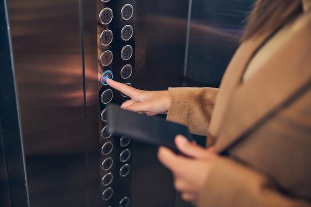 내려갈 리프트의 버튼을 누르면 갈색 코트에 여자의 사진을 닫습니다