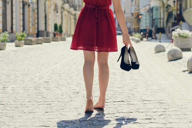 빨간 우아한 드레스를 입은 여성이 하이힐 신발을 손에 들고 맨발로 걷는 사진을 닫고 뒤에서, 도시를 배경으로 봅니다.