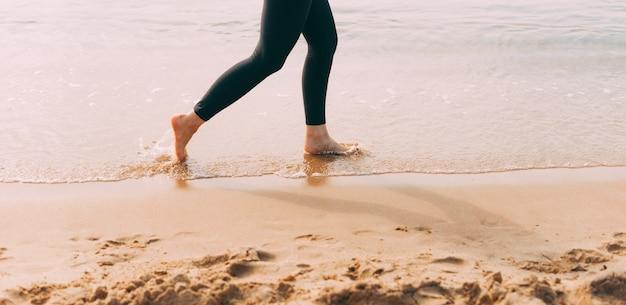 Крупным планом фото ног женщины, бегущей на пляже во время заката