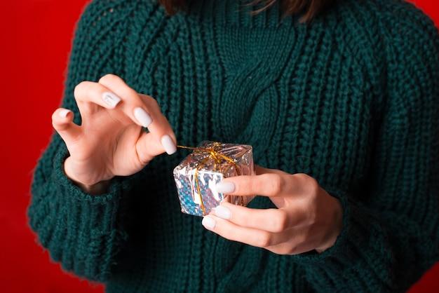 작은 선물을 여는 여자의 사진을 닫습니다