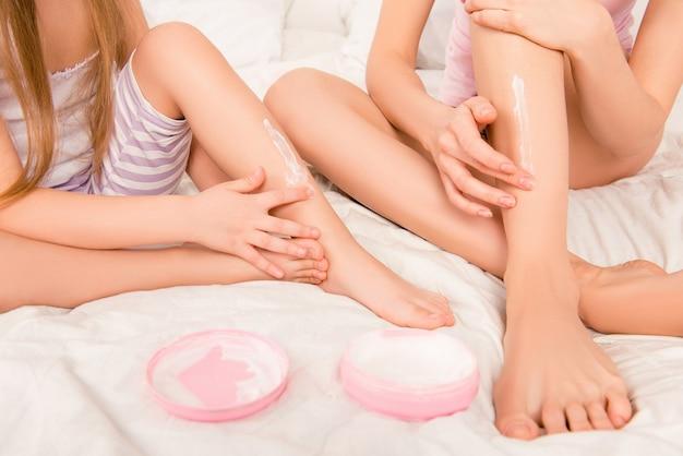 クリームを塗った女性と子供の足のクローズアップ写真