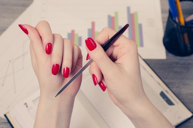 Крупным планом фото руки женщины, исправляющей ноготь с помощью гвоздя на работе