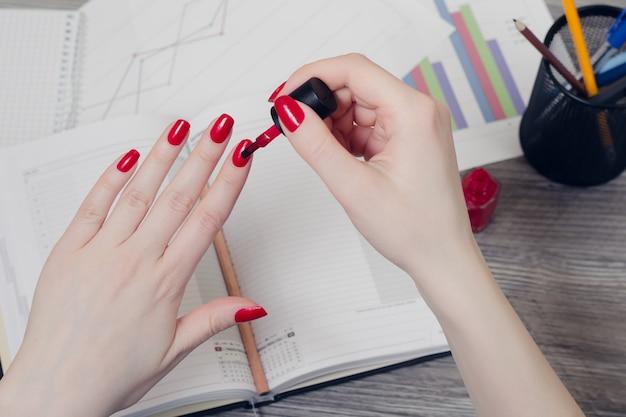 Крупным планом фото женских рук, красящих ногти, над рабочим столом с блокнотом и графиками