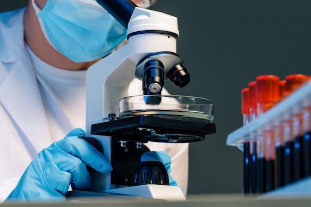 현미경을 사용하는 여성 과학자의 사진을 닫습니다